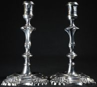 A pair of 18th century Irish cast silver candlesticks, reel shaped sconces, knopped pillars,