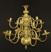 A William and Mary style brass twelve light chandelier, reel shaped sconces, dished wax pans, scroll