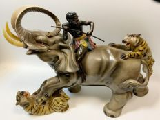 A retro hollow cast model, tribesmen riding an elephant being attacked by a pair of tigers, 35.5cm