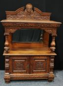 A late Victorian oak pier/side cabinet, arched pediment centred by a carved mask, above a