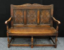 A 17th century style oak bench/settle, shaped cresting rail carved with acanthus, above a three