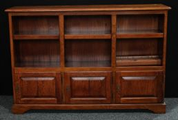 An early 20th century oak open bookcase, rectangular top above adjustable shelves and three cupboard