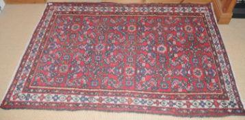 A Middle Eastern woollen rug, with geometrical motifs, 162cm x 110cm