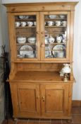 A 19th century pine dresser, moulded cornice, above two glazed cupboard doors, the projecting base