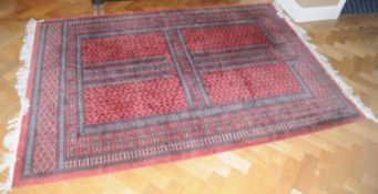 A Middle Eastern woollen rug, woven with geometrical panels, 188cm x 130cm