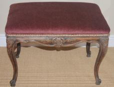 A 19th century stool, stuffed over top, the apron and cabriole legs carved with flowers, 43cm