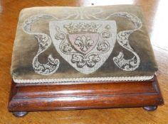 A Victorian foot stool, the velvet top with crest, ogee sides, bun feet, 32cm wide, 25cm deep, c.