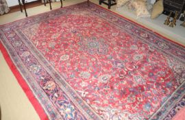 A Middle Eastern woollen rug, with central medallion, and scrolling foliage on a red ground, 315cm