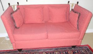 A Knowle sofa, upholstered in rust red, lobed feet, 168cm wide