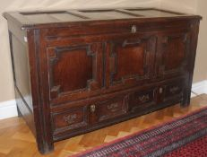 An 18th century oak blanket chest, with panelled top, above field panelled front and two drawers,