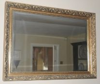 A contemporary rectangular mirror, the frame moulded with scrolls, 84cm wide, 60cm high