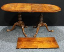 A George III style mahogany dining table, oval top, carved twin pedestals, one additional leaf, 74cm