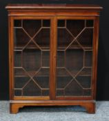 A mid 20th century mahogany bookcase, rectangular top above a pair of astral glazed doors