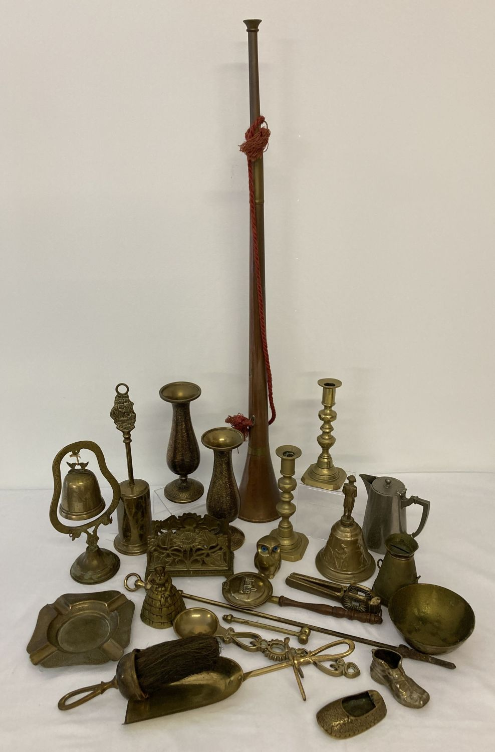 Lot 1122 - A box of mixed metal ware to include brass candlesticks, vases & bells and a copper hunting horn.