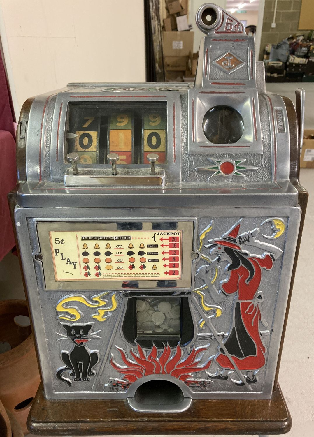 """A """"One Arm Bandit"""" 3 wheel slot machine in witch and cat design, marked with Jennings logo."""