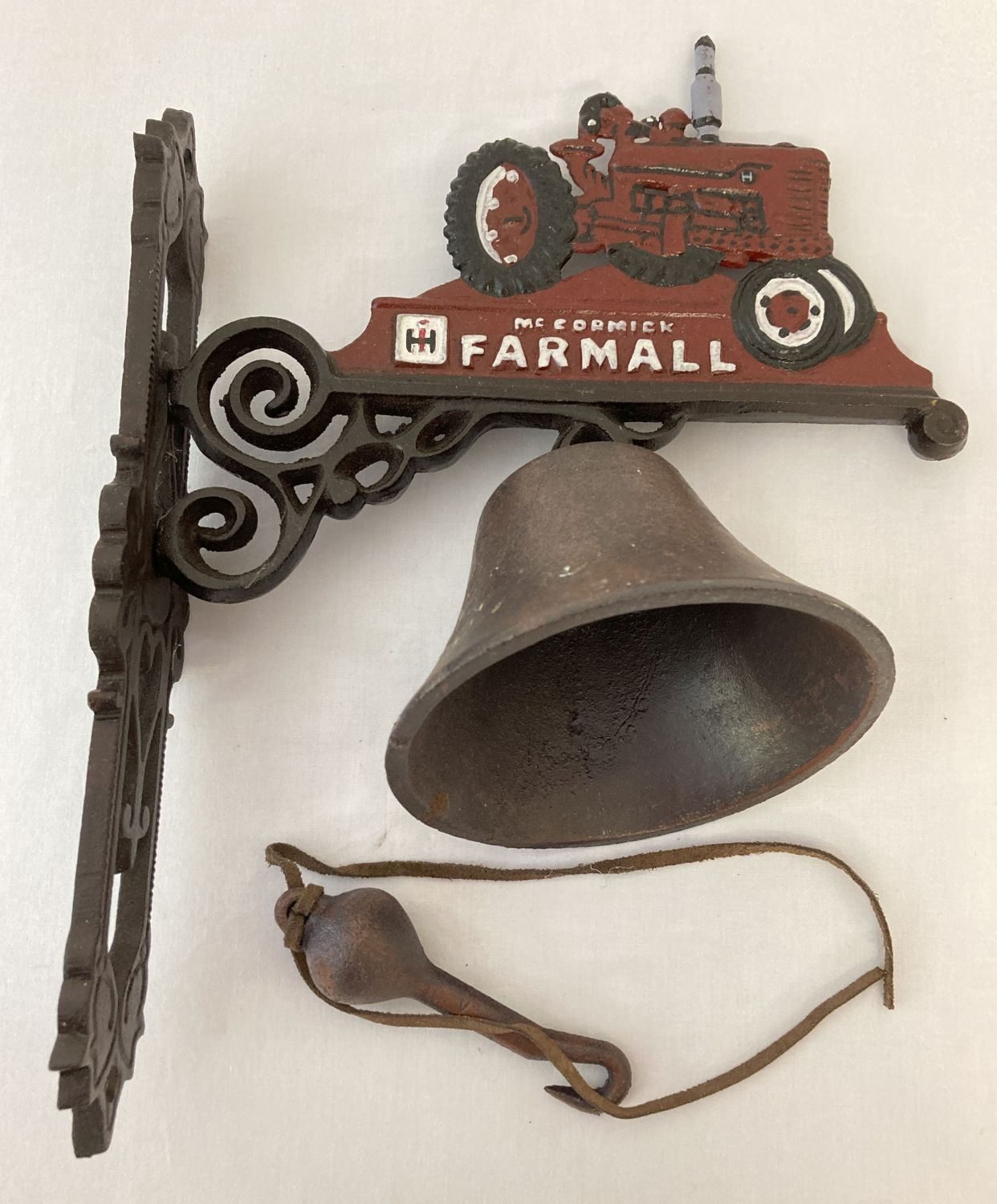 """Lot 1117 - A painted cast iron wall hanging bell with """"McCormick Farmall"""" logo and tractor."""