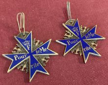 2 reproduction Pour Le Merite medals with blue enamel finish and eagle detail.