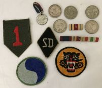 A badge of assorted military embroidered patches, ribbons and coins.