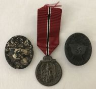 A WWII style German Eastern Front medal and ribbon, together with 2 pin back wound badges.