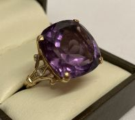 A 9ct gold amethyst and diamond dress ring with large cushion cut central amethyst.