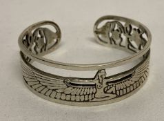 A decorative white metal open work bangle with Egyptian goddess Isis and scarab beetle detail.