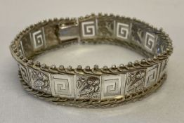 A flexible silver panel bracelet with owl and Greek key decoration. Clasp needs attention.