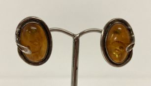 A pair of silver and amber stud style earrings with Art Nouveau style decoration.