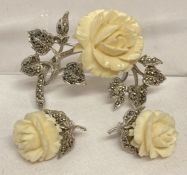 A vintage matching brooch and clip on earrings with carved rose detail and set with marcasites.