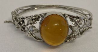 A Polish silver decorative bangle set with central Baltic amber cabochon with push clasp.