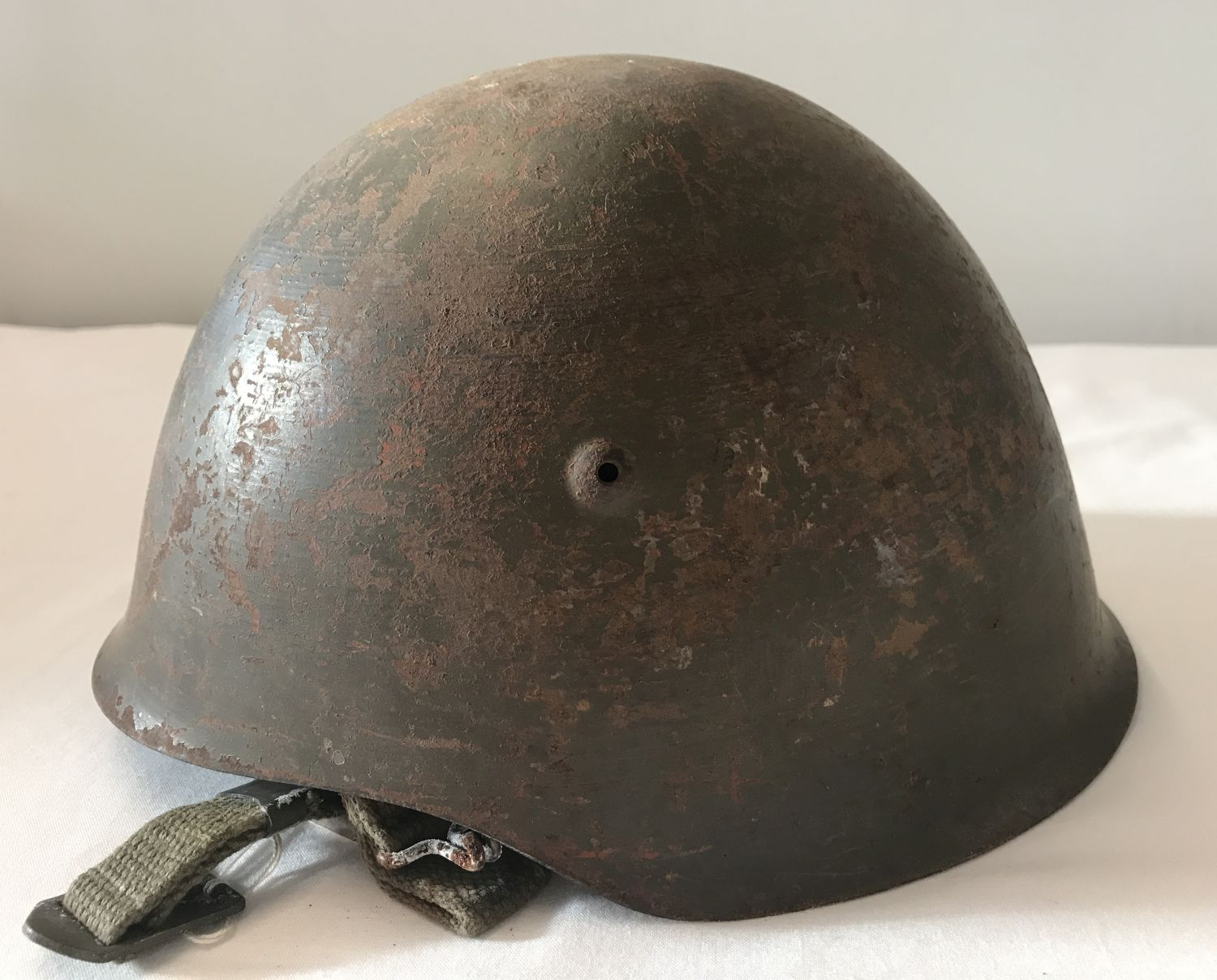 Lot 116 - An M1940 - 63 Portuguese steel helmet, complete with canvas lining and chin strap.