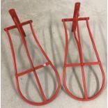 2 wall mountable saddle racks, painted red.
