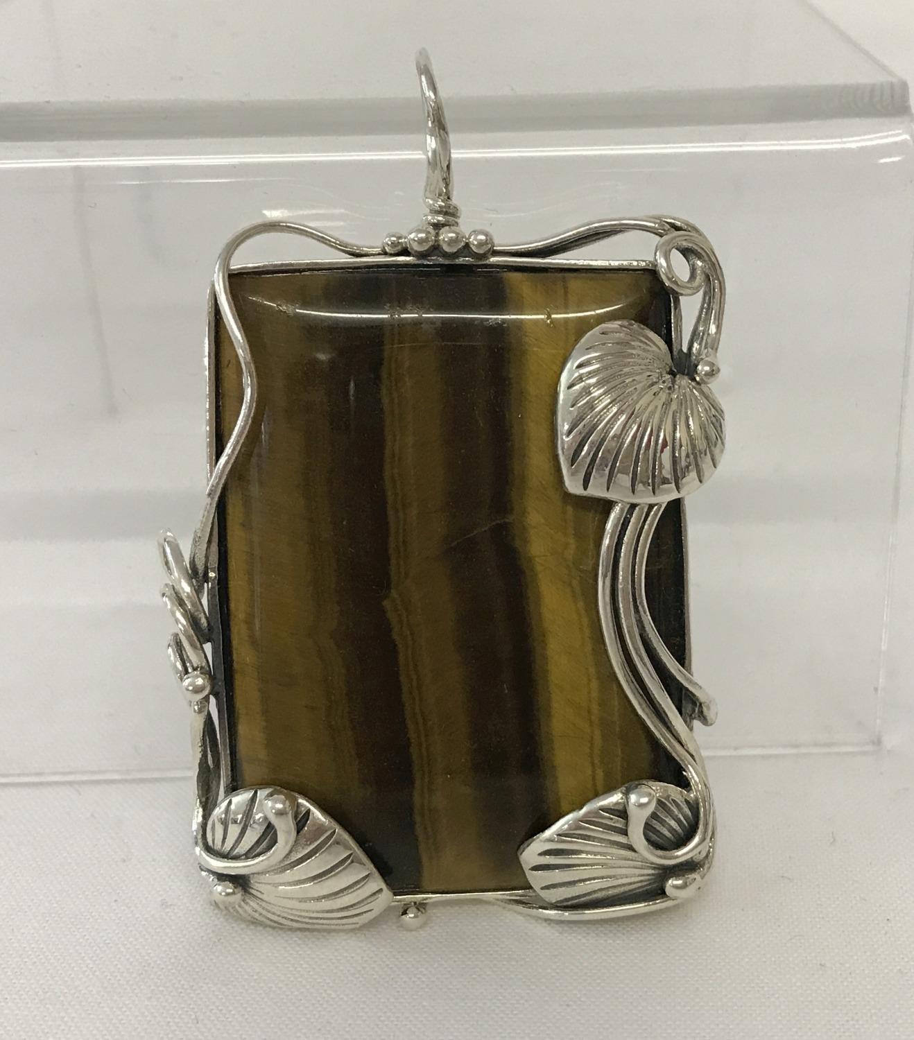 Lot 1095 - A large rectangular shaped Tiger's eye pendant framed in an Art Nouveau style 925 silver mount.