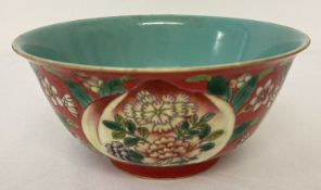 A Chinese ceramic bowl with decorative outer bowl and blue/green glaze interior.