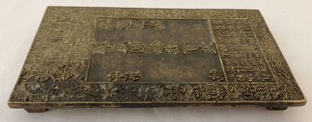 A large Chinese brass rectangular shaped scroll weight with Chinese symbol detailing to top.