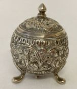 A Persian silver 3 footed pepperette of spherical form, with ornate floral decoration throughout.