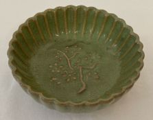 A small dark green glazed bowl with scalloped sides and tree detail to interior.