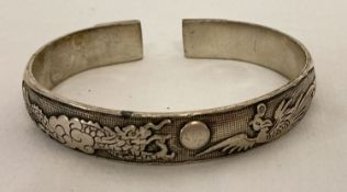 A Chinese white metal bangle featuring a dragon and a phoenix.
