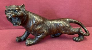 A hollow bronze figurine of a roaring tiger.
