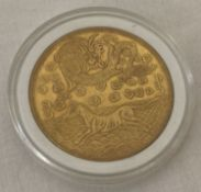 A gold coloured Chinese coin in a clear plastic case.