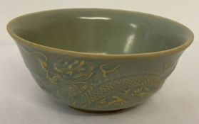 A Chinese ceramic bowl with pale blue glaze and dragon and phoenix design to outer bowl.