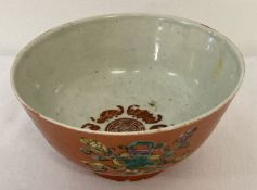 A Chinese tea bowl with orange glaze to outer bowl and fu bat detail to interior.