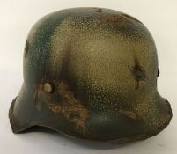 A German WWII style M42 Normandy helmet with painted camo detail.