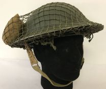 A WWII style British Brodie helmet with cam net and field dressing.