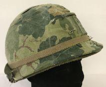 "A Vietnam War era US M1 helmet with reversible ""Mitch"" camo cover and original Vietnam War era liner"