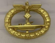 A reproduction German Kreigsmarine submarine badge in gold tone.