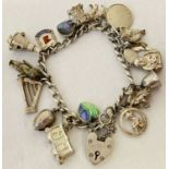 A vintage silver charm bracelet with 17 silver and white metal charms, complete with safety chain.
