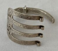 A silver bangle made from a decorative Victorian serving fork.