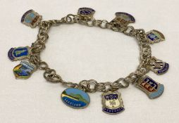 A vintage silver double belcher chain charm bracelet with 10 enamelled silver town & county charms.