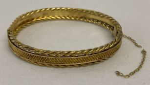 A gold bangle with diamond shaped decoration to centre and twisted rope details to both edges.