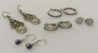 5 pairs of silver and white metal earrings in drop, stud and hoops styles.